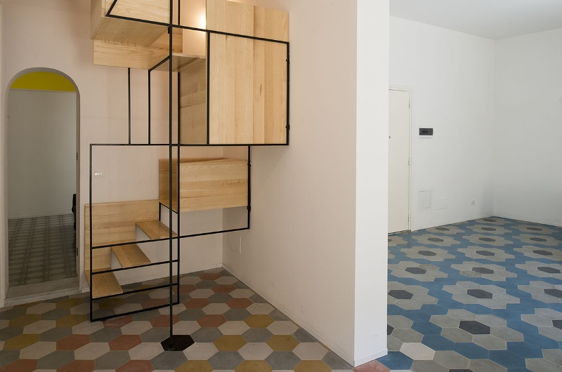 Escalera escultural conecta dos pisos de mosaico en la casa de un ...